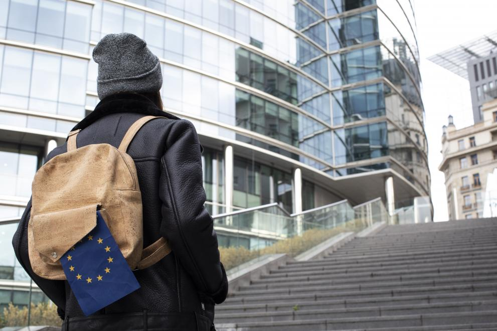Young girl walking with EU flag on her ruck sack